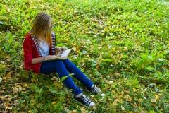 Muchacha que se sienta en hierba y que lee un libro Foto de archivo libre de regalías