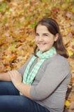 muchacha que se sienta en hojas Imagen de archivo libre de regalías