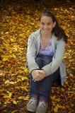 Muchacha que se sienta en hojas de otoño Imagenes de archivo