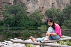 Muchacha que se sienta en la balsa de bambú Foto de archivo libre de regalías