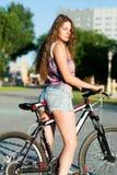 Muchacha que se sienta en la bicicleta Imágenes de archivo libres de regalías