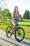 Muchacha que se sienta en la bicicleta Fotos de archivo libres de regalías