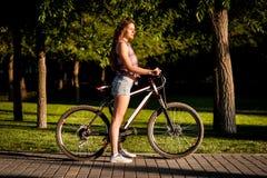 Muchacha que se sienta en la bicicleta Foto de archivo libre de regalías