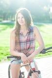Muchacha que se sienta en la bicicleta Imagenes de archivo