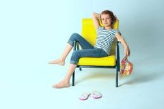 Muchacha que se sienta en la butaca amarilla sobre fondo azul Fotos de archivo