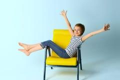Muchacha que se sienta en la butaca amarilla sobre fondo azul Imagenes de archivo