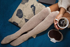 Muchacha que se sienta en la cama con una taza de café Fotografía de archivo