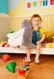 Muchacha que se sienta en la cama de bebé con los muchachos imagen de archivo libre de regalías