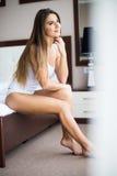 Muchacha que se sienta en la cama en casa que despierta Imagenes de archivo