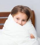 Muchacha que se sienta en la cama envuelta en una manta Imágenes de archivo libres de regalías