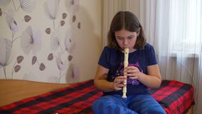 Muchacha que se sienta en la cama y la flauta practicante metrajes