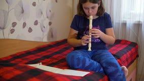 Muchacha que se sienta en la cama y que toca la flauta almacen de metraje de vídeo