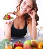 Muchacha que se sienta en la cocina en el escritorio con la fruta y los vidrios con el jugo Fotografía de archivo