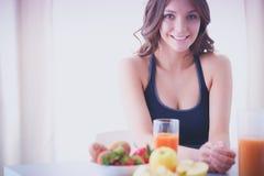 Muchacha que se sienta en la cocina en el escritorio con la fruta y los vidrios con el jugo Imagen de archivo