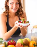 Muchacha que se sienta en la cocina en el escritorio con la fruta y los vidrios con el jugo Imagenes de archivo