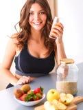 Muchacha que se sienta en la cocina en el escritorio con la fruta y los vidrios con el jugo Fotos de archivo libres de regalías
