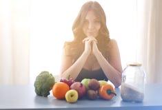 Muchacha que se sienta en la cocina en el escritorio con la fruta y los vidrios con el jugo Foto de archivo libre de regalías