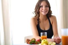 Muchacha que se sienta en la cocina en el escritorio con la fruta y los vidrios con el jugo Imágenes de archivo libres de regalías