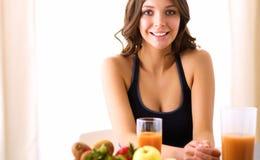 Muchacha que se sienta en la cocina en el escritorio con la fruta y los vidrios con el jugo Foto de archivo