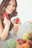 Muchacha que se sienta en la cocina en el escritorio con la fruta y los vidrios con el jugo Imagen de archivo libre de regalías