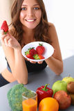 Muchacha que se sienta en la cocina en el escritorio con la fruta Foto de archivo