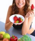 Muchacha que se sienta en la cocina en el escritorio con la fruta Foto de archivo libre de regalías