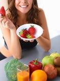 Muchacha que se sienta en la cocina en el escritorio con la fruta Fotos de archivo libres de regalías