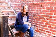 Muchacha que se sienta en la escalera, al lado de la pared de ladrillo roja Imagen de archivo