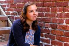 Muchacha que se sienta en la escalera, al lado de la pared de ladrillo roja Imagenes de archivo