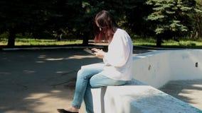 Muchacha que se sienta en la fuente en el parque, juegos el juego almacen de metraje de vídeo