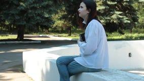 Muchacha que se sienta en la fuente en parque, controles el libro en sus manos y el sueño almacen de metraje de vídeo