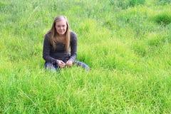 Muchacha que se sienta en la hierba. Fotografía de archivo libre de regalías