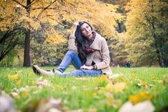 Muchacha que se sienta en la hierba Fotos de archivo libres de regalías