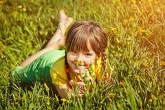 Muchacha que se sienta en la hierba con el diente de león Imagenes de archivo