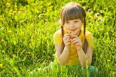 Muchacha que se sienta en la hierba con el diente de león Imágenes de archivo libres de regalías