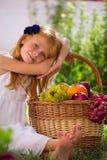 Muchacha que se sienta en la hierba con una cesta de fruta Imagen de archivo libre de regalías