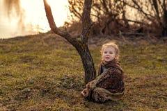 Muchacha que se sienta en la hierba de la primavera imagen de archivo