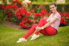 Muchacha que se sienta en la hierba en el verde del verano del parque Imágenes de archivo libres de regalías