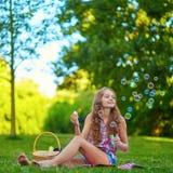 Muchacha que se sienta en la hierba y las burbujas que soplan Fotografía de archivo