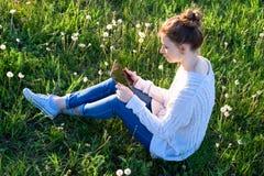 Muchacha que se sienta en la hierba y que mira la tableta Imagen de archivo libre de regalías