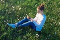 Muchacha que se sienta en la hierba y que mira la tableta Imagenes de archivo
