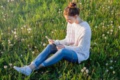 Muchacha que se sienta en la hierba y que mira la tableta Fotos de archivo libres de regalías