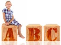 Muchacha que se sienta en la letra A B C Fotos de archivo libres de regalías