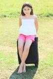 Muchacha que se sienta en la maleta Foto de archivo