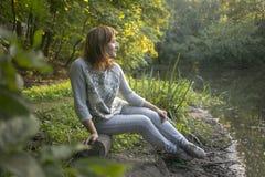 Muchacha que se sienta en la orilla del lago Imagenes de archivo