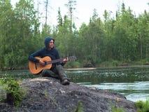 Muchacha que se sienta en la orilla del río con una guitarra Imagen de archivo libre de regalías