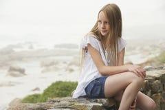 Muchacha que se sienta en la pared de piedra Imágenes de archivo libres de regalías