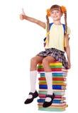 Muchacha que se sienta en la pila de libros que muestran el pulgar para arriba. Fotografía de archivo libre de regalías