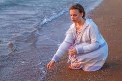 Muchacha que se sienta en la playa en la playa imagenes de archivo