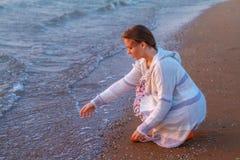 Muchacha que se sienta en la playa en la playa fotografía de archivo libre de regalías